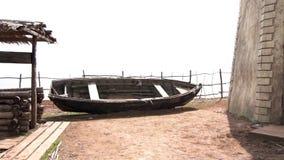 Παλαιά μαύρη ξύλινη βάρκα με ένα one-storey σπίτι, καλά και ένας λόφος στο ρωσικό χωριό Cossack βίντεο Ένας παλαιός απόθεμα βίντεο