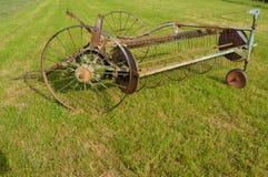 Παλαιά μηχανή ξηραντών σανού σε έναν τομέα στοκ εικόνες