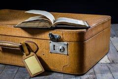Παλαιά μοντέρνη βαλίτσα Παλαιά βιβλία σε μια βαλίτσα Βαλίτσα σε έναν ξύλινο πίνακα Στοκ φωτογραφία με δικαίωμα ελεύθερης χρήσης