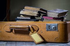 Παλαιά μοντέρνη βαλίτσα Παλαιά βιβλία σε μια βαλίτσα Βαλίτσα σε έναν ξύλινο πίνακα Στοκ Φωτογραφία