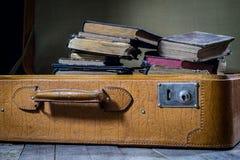 Παλαιά μοντέρνη βαλίτσα Παλαιά βιβλία σε μια βαλίτσα Βαλίτσα σε έναν ξύλινο πίνακα Στοκ Εικόνες