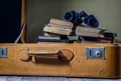 Παλαιά μοντέρνη βαλίτσα Παλαιά βιβλία σε μια βαλίτσα Βαλίτσα σε έναν ξύλινο πίνακα Στοκ εικόνες με δικαίωμα ελεύθερης χρήσης