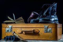 Παλαιά μοντέρνη βαλίτσα Στρατιωτικά λασπώδη παπούτσια σε μια βαλίτσα Βαλίτσα σε έναν ξύλινο πίνακα Στοκ εικόνα με δικαίωμα ελεύθερης χρήσης