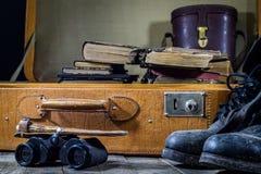 Παλαιά μοντέρνη βαλίτσα Στρατιωτικά λασπώδη παπούτσια σε μια βαλίτσα Βαλίτσα σε έναν ξύλινο πίνακα Στοκ Εικόνα