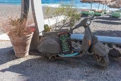 Παλαιά μοτοσικλέτα με τον πίνακα για τα κοκτέιλ μπροστά από έναν φραγμό παραλιών Στοκ Εικόνες