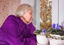 Παλαιά μόνη συνεδρίαση γυναικών κοντά στο παράθυρο στο σπίτι του Στοκ εικόνα με δικαίωμα ελεύθερης χρήσης