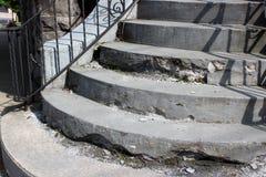 Παλαιά, ξεπερασμένα βήματα πετρών που έχουν ανάγκη από επισκευή, με το μαύρο κιγκλίδωμα επεξεργασμένου σιδήρου για την υποστήριξη Στοκ Εικόνα