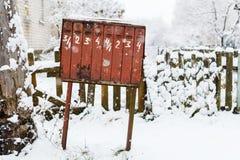 Παλαιά ξεχαρβαλωμένη ταχυδρομική θυρίδα το χειμώνα κάτω από το χιόνι Στοκ Εικόνες
