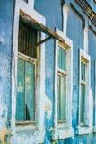 Παλαιά ξύλινα παράθυρα στον τοίχο του μπλε κτηρίου που φθείρεται με το χρόνο και τις καιρικές συνθήκες στοκ εικόνες
