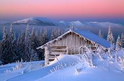 Παλαιά ξύλινη καλύβα Τεράστια snowdrifts γύρω Υπόβαθρο των υψηλών βουνών Τα υψηλά fairtrees με snowflakes Στοκ Εικόνες
