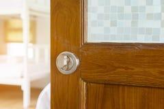 Παλαιά ξύλινη πόρτα ανοικτή με τη σύγχρονα λαβή πορτών και το δωμάτιο θαμπάδων Στοκ Φωτογραφία