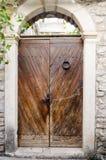 Παλαιά ξύλινη πόρτα, σχηματισμένος αψίδα τοίχος πετρών Αγροτικό και αναδρομικό ύφος στοκ εικόνες