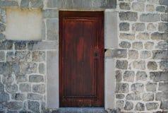 Παλαιά ξύλινη πόρτα, σχηματισμένος αψίδα τοίχος πετρών Αγροτικό και αναδρομικό ύφος στοκ εικόνα