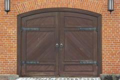 Παλαιά ξύλινη πύλη στο τουβλότοιχο στοκ εικόνα με δικαίωμα ελεύθερης χρήσης