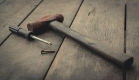 Παλαιά οξυδωμένα σφυρί, κατσαβίδι και καρφί στον παλαιό ξύλινο πίνακα Εργαλεία ξυλουργικής για την αποτύπωση και το σπίτι επισκευ στοκ φωτογραφία