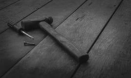Παλαιά οξυδωμένα σφυρί, κατσαβίδι και καρφί στον παλαιό ξύλινο πίνακα Εργαλεία ξυλουργικής για την αποτύπωση και το σπίτι επισκευ στοκ φωτογραφία με δικαίωμα ελεύθερης χρήσης
