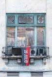 Παλαιά παράθυρα που θέτουν με το κόκκινο και τη μαύρη σημαία Στοκ Εικόνες