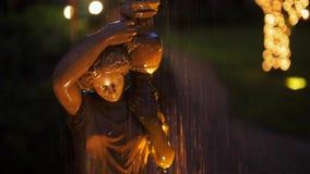Παλαιά πηγή με το πέτρινο άγαλμα μιας γυναίκας με ένα βάζο στον κήπο στη νύχτα φιλμ μικρού μήκους