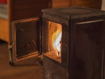 Παλαιά πόρτα σομπών μετάλλων ανοικτή με το κάψιμο του ξύλου φλογών Στοκ εικόνες με δικαίωμα ελεύθερης χρήσης