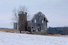 Παλαιά σιταποθήκη και σιλό στο χιονισμένο τομέα στοκ φωτογραφία με δικαίωμα ελεύθερης χρήσης