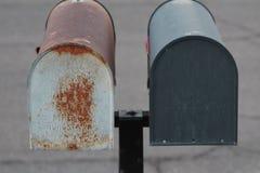 Παλαιά σκουριασμένη ταχυδρομική θυρίδα δίπλα στη νέα μαύρη ταχυδρομική θυρίδα Στοκ Εικόνες