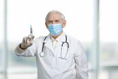 Παλαιά σοβαρή σύριγγα εκμετάλλευσης γιατρών με το εμβόλιο στοκ φωτογραφία με δικαίωμα ελεύθερης χρήσης