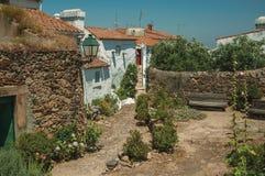 Παλαιά σπίτια με τον ασπρισμένο τοίχο σε μια αλέα με τα λουλούδια στοκ εικόνες με δικαίωμα ελεύθερης χρήσης