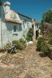 Παλαιά σπίτια με τον ασπρισμένο τοίχο σε μια αλέα με τα λουλούδια στοκ φωτογραφίες