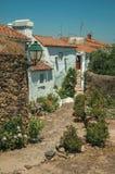 Παλαιά σπίτια με τον ασπρισμένο τοίχο σε μια αλέα με τα λουλούδια στοκ εικόνες