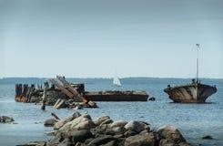 Παλαιά σπασμένα συντρίμμια βαρκών στην ακτή, την μπλε θάλασσα και sailboat στο υπόβαθρο Στοκ εικόνες με δικαίωμα ελεύθερης χρήσης