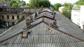 Παλαιά στέγη με τις καπνοδόχους, καθώς επίσης και μια στέγη που καταστρέφεται από τις πυρκαγιές σε ένα παλαιό σπίτι στην πόλη της φιλμ μικρού μήκους