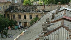 Παλαιά στέγη με τις καπνοδόχους, καθώς επίσης και μια στέγη που καταστρέφεται από τις πυρκαγιές σε ένα παλαιό σπίτι στην πόλη της απόθεμα βίντεο
