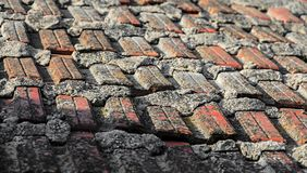 Παλαιά τοπ στέγη σπιτιών με τα κόκκινα πορτοκαλιά κεραμικά κεραμίδια σχεδίων, σύσταση Στοκ φωτογραφίες με δικαίωμα ελεύθερης χρήσης
