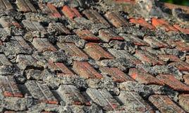 Παλαιά τοπ στέγη σπιτιών με τα κόκκινα πορτοκαλιά κεραμικά κεραμίδια σχεδίων, σύσταση Στοκ Εικόνες
