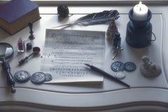 Παλαιά υλικά γραψίματος και ένα κερί στον πίνακα στοκ εικόνες