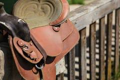Παλαιά φορεμένη σέλα αλόγων δέρματος στον ξύλινο φράκτη, αναμμένο από τον ήλιο στοκ φωτογραφία με δικαίωμα ελεύθερης χρήσης