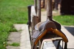 Παλαιά φορεμένη σέλα αλόγων που βάζει στον ξύλινο φράκτη αναμμένο από τον ήλιο στοκ φωτογραφία με δικαίωμα ελεύθερης χρήσης