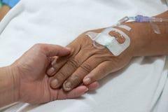 Παλαιά χέρια που κρατούν το ένα το άλλο με IV λύση Στοκ Φωτογραφία