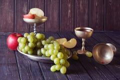 Παλαιά goblets μετάλλων με το κόκκινο κρασί, δέσμη των σταφυλιών και των μήλων, Στοκ εικόνες με δικαίωμα ελεύθερης χρήσης