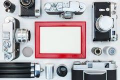 Παλαιές αναδρομικές κάμερες, ταινίες ρόλων, τρίποδο και κόκκινο πλαίσιο φωτογραφιών Παλαιό μ Στοκ Φωτογραφία