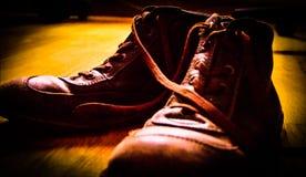 παλαιές καφετιές μπότες ημίφωτός στοκ εικόνες