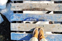 Παλαιές μπλε ξύλινες μπότες αποβαθρών και χειμώνα στοκ εικόνες