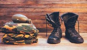 Παλαιές μπότες αστραγάλων μποτών μαύρων δέρματος, στρατιωτικές στολές και μια φιάλη του νερού στο ξύλινο υπόβαθρο στοκ φωτογραφίες