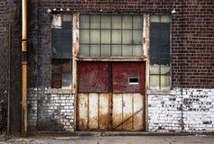 Παλαιές οξυδωμένες πόρτες μετάλλων στο εγκαταλειμμένο αποσυντιθειμένος κτήριο εργοστασίων τούβλου στοκ εικόνες