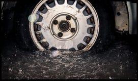 Παλαιές οξυδωμένες ρόδα και ρόδα από ένα παλαιό αυτοκίνητο που παίρνει πλημμυρισμένο από το φ Στοκ Φωτογραφία