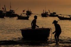 Παλαιές σκιαγραφίες ψαράδων και αγοριών στη στρογγυλή βάρκα στο ηλιοβασίλεμα Στοκ Εικόνα