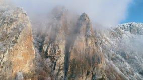 Παλαιοί απότομοι βράχοι κοντά στην κορυφή των βουνών που καλύπτονται από τα παγωμένα κωνοφόρα δέντρα στα γκρίζα σύννεφα ενάντια σ φιλμ μικρού μήκους