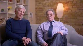 Παλαιοί αρσενικοί φίλοι που κάθονται μαζί στον καναπέ και που μιλούν ενθουσιωδώς και σοβαρά απόθεμα βίντεο