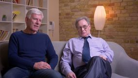 Παλαιοί αρσενικοί φίλοι που κάθονται μαζί στον καναπέ που προσέχει τη TV και που λέει τις αστείες ιστορίες που είναι χαρούμενες φιλμ μικρού μήκους