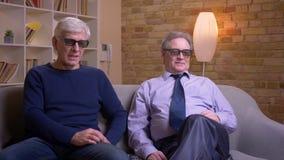 Παλαιοί αρσενικοί φίλοι στα τρισδιάστατα γυαλιά που προσέχουν τον κινηματογράφο μαζί στη TV και που σχολιάζουν χαρωπά απόθεμα βίντεο